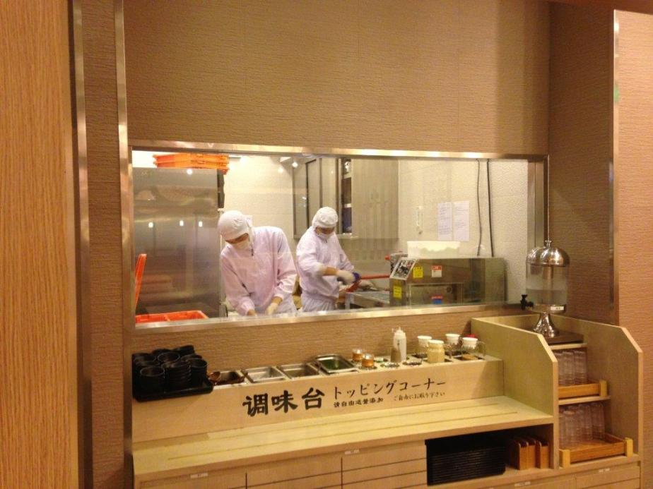 Behind the scene are 2 workers making fresh udon and in front is the sauces station and free cold water on the right