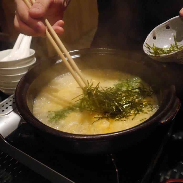 Towards the end, the broth is thickened with egg and rice is added for a rich concoction of nutritious porridge.