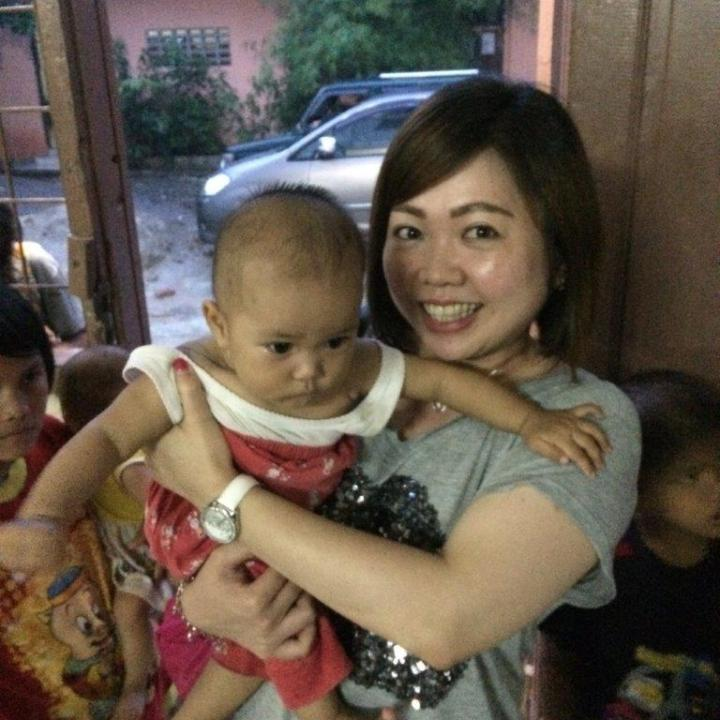 Wiwi cuddling an orphan who was left at the doorstep of the orpahanage